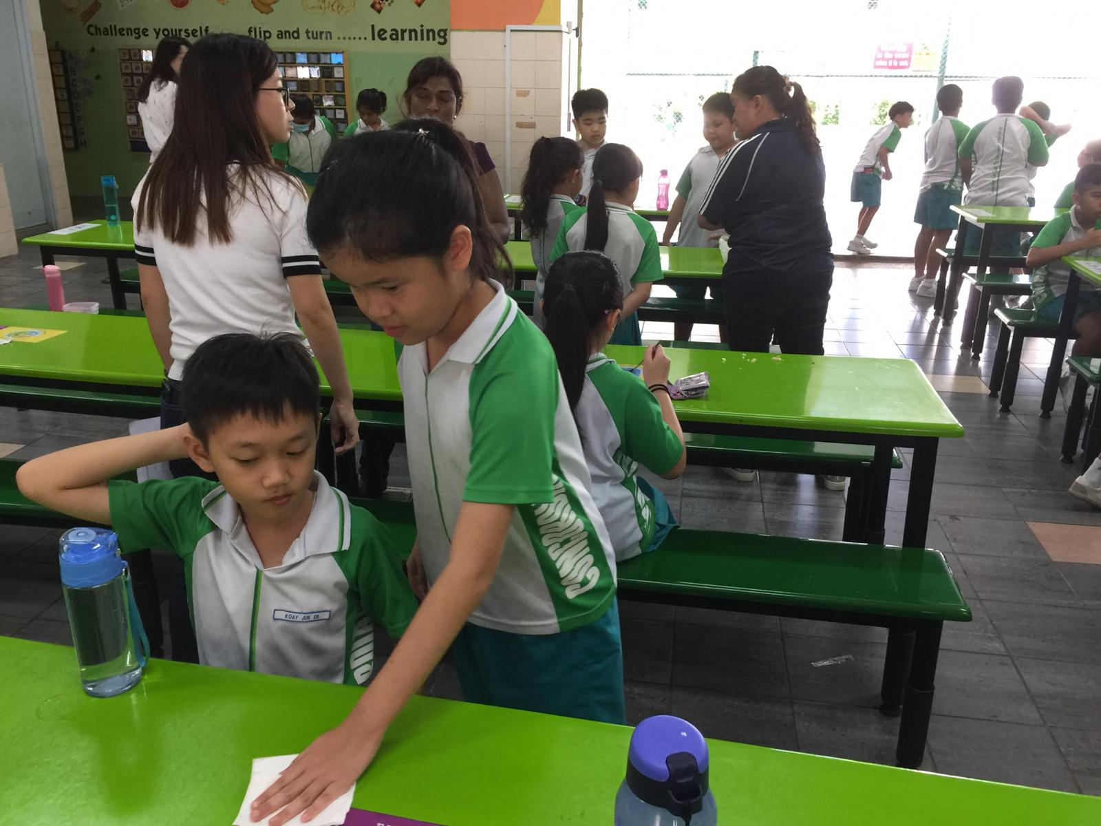 A student showing her classmate how to do the Wipe-Down Routine.jpeg